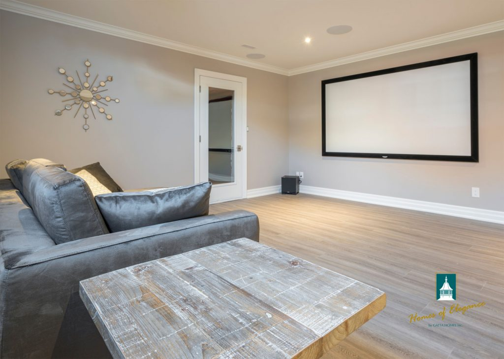 A basement rec room with a table, couch and television, showing off vinyl plank flooring