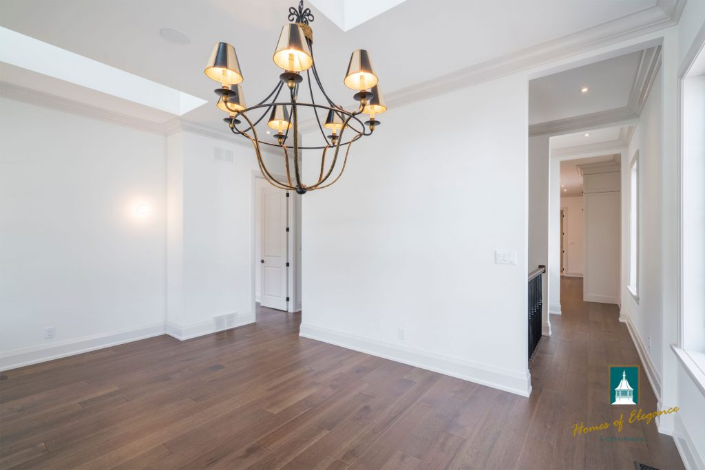 Solid hardwood flooring in an empty room with a prominent lighting fixture