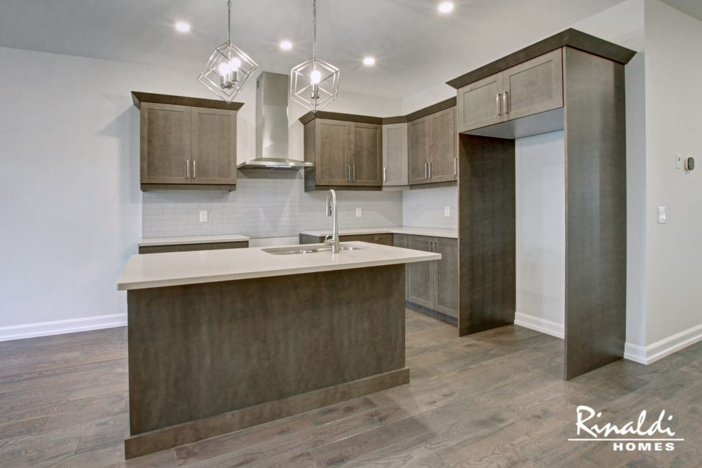 A kitchen in a model home with hardwood flooring