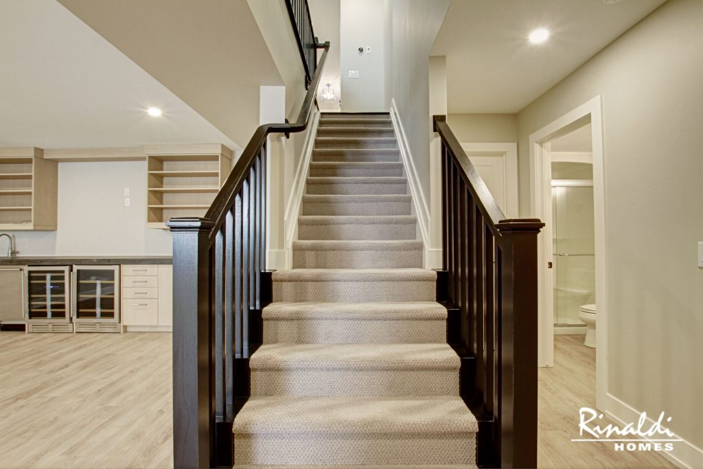 A carpet stair runner on stairs leading to a basement