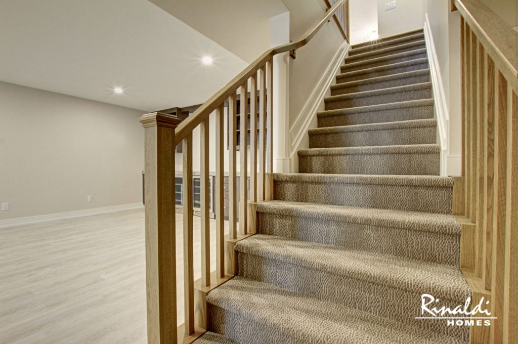 Stairs lined with a carpet stair runner leading to a basement